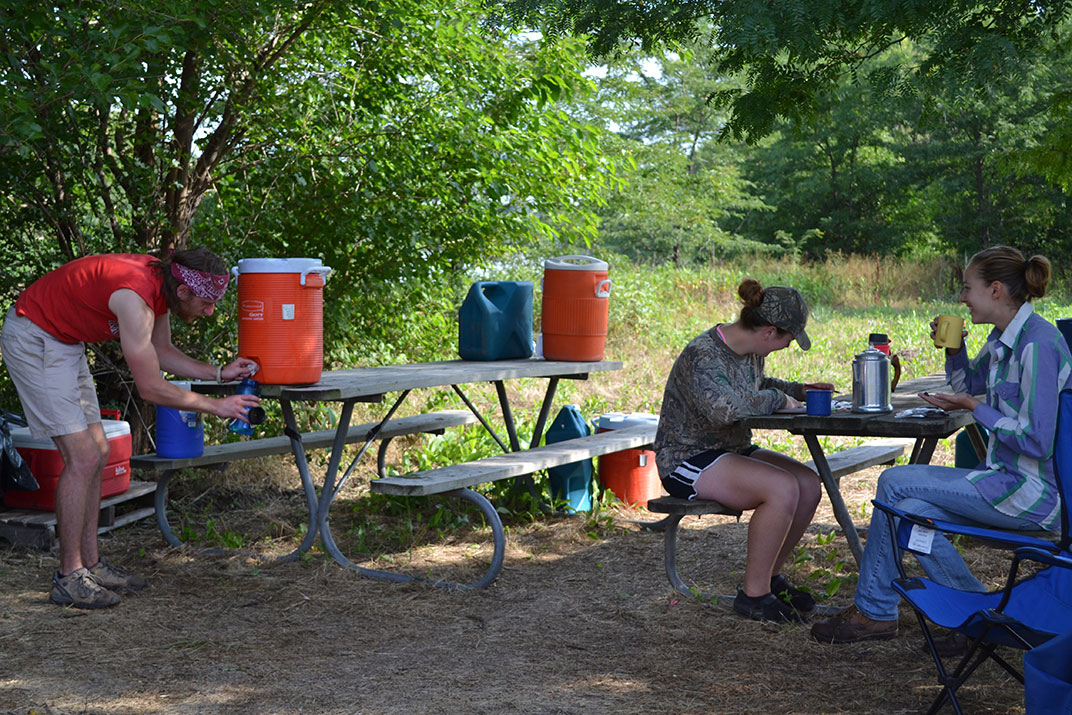 Workers at picnic tables in shade.